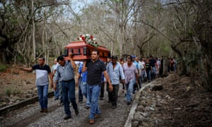 Members of the Solecito search group carry the coffin of Pedro Huesca, a police detective who disappeared in 2013 and was found in a mass grave, in Veracruz. Veracruz state prosecutor Jorge Winckler said investigators found 114 ID cards in the field, which held about 32 burial pits.
