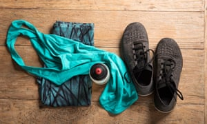 Flatlay of sports kit, bottles and shoes on wooden floor