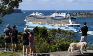 People watch a cruise ship leave Sydney harbour through the headlands