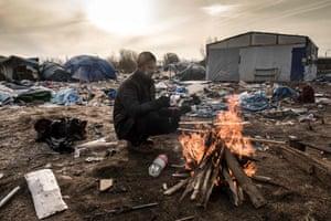 Hemn, a Kurd, keeps warm next to a fire