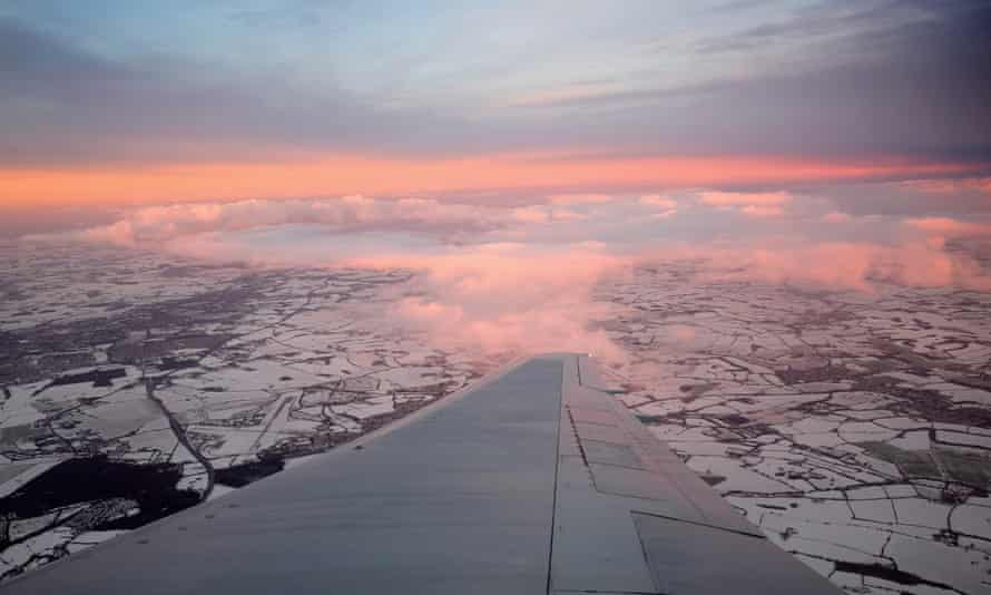 View of snow-covered fields and wing in foreground from British Airways plane