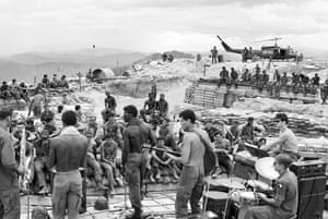 GIs of the 3rd Brigade, 101st Airborne Division, launch into a rock session while surrounded by symbols of the war: wooden bunkers, helicopter, and sandbags, July 1970
