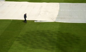 A groundsman looks to help clear the water with the sun shining above.