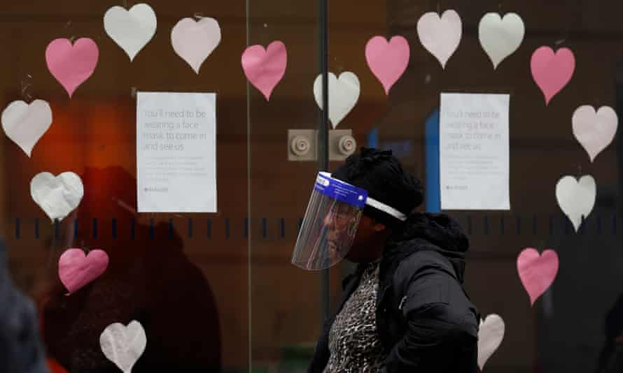A woman wearing queues outside a Leicester bank.