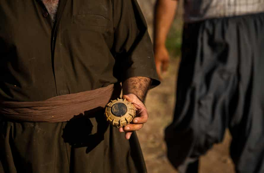 Rizgar Ali holds a landmine he removed from a villager's property after the villager waved down Ali's brother, landmine deminer Hoshyar Ali, who drove past the man's house at Serdera Village near Penjwen, Iraqi Kurdistan