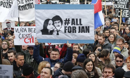 A man holds up a placard depicting Jan Kuciak and Martina Kusnirova during a march celebrating the resignation of the Slovakian PM Robert Fico in March 2018.