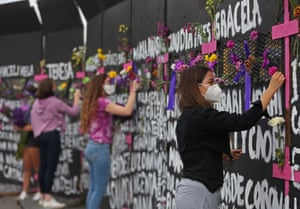 Women place flowers and posters with the names of victims of femicide on a fence placed front of the National Palace in Mexico City, Mexico