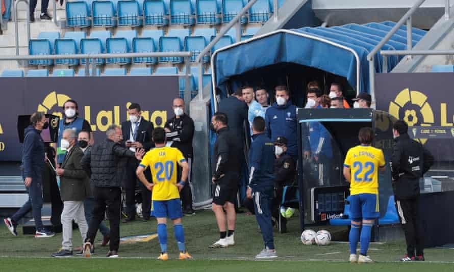 Cádiz players wait on the touchline after Valencia left the field on Sunday.
