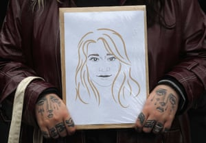 A demonstrator holds a drawing of Sarah Everard near New Scotland Yard.