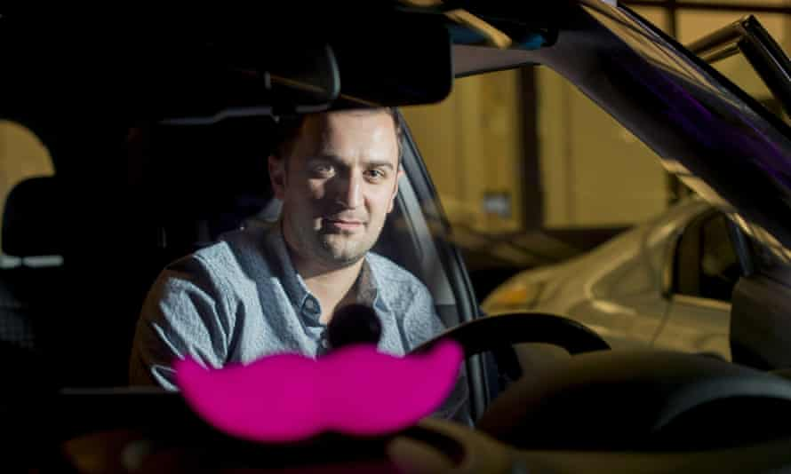 Lyft co-founder John Zimmer displays his company's 'glowstache' at an event in San Francisco.