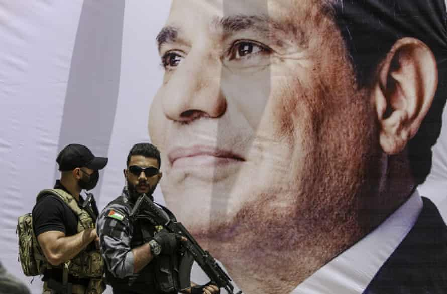 Two members of the Egyptian security forces stand guard beside a banner showing a photo of President Abdel Fatah al-Sisi.