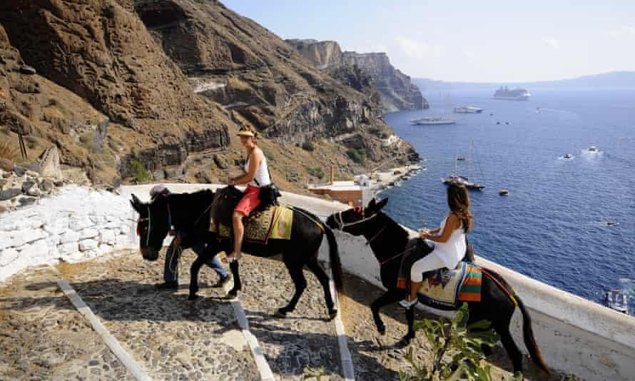 Tourists riding donkeys in Santorini