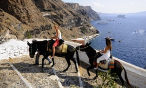 Tourists riding donkeys in Fira, island of Santorini.