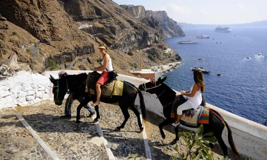Tourists riding donkeys in Fira, island of Santorini.