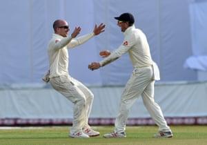 England's Jack Leach (L) celebrates with his teammate Jos Buttler after dismissing Sri Lanka's Dilruwan Perera.