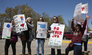Teachers from Apollo elementary school in the Putnam City school district of Oklahoma City, wave signs at passing cars outside the state capitol as protests over school funding continue on Wednesday.