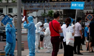 Medical staff carry signs to assist people who live near or who have visited the Xinfadi Market in Beijing on June 17, 2020