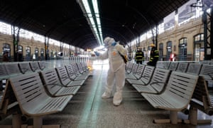 A Spanish soldier disinfects a railway station in Valencia on Monday after the government placed the country in lockdown on Saturday.