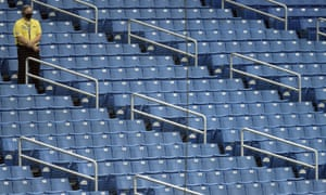 A security guards stands over empty seats during the fourth inning of a baseball game between the Tampa Bay Rays and the Toronto Blue Jays Sunday in Florida.
