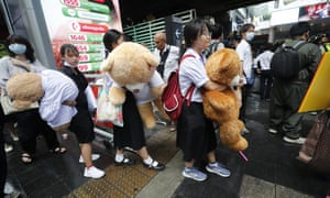 High school students hold giant teddy bears as they attend a bad student rally in Bangkok on Saturday.