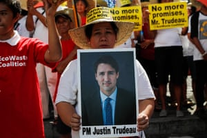 A woman holds a portrait of Canadian Prime Minister Justin Trudeau during a protest outside the Canadian Embassy