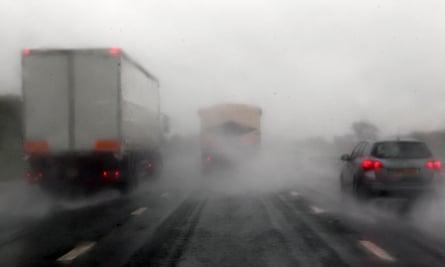Vehicles drive in the rain