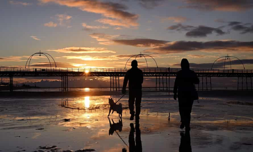 People walk with a dog along the beach at sunset, near Southport Pier, UK