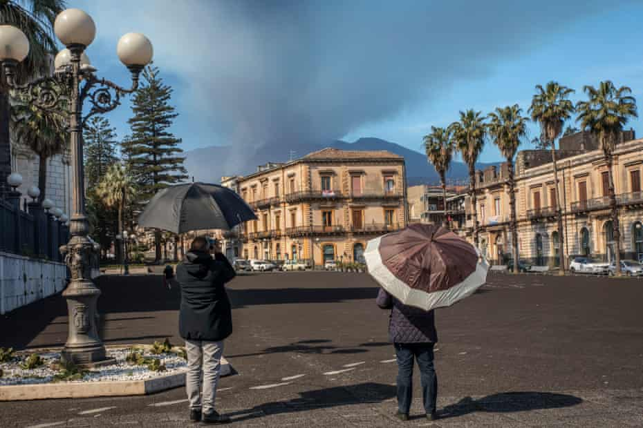 People in the town of Giarre use umbrellas as protection against volcanic ash.