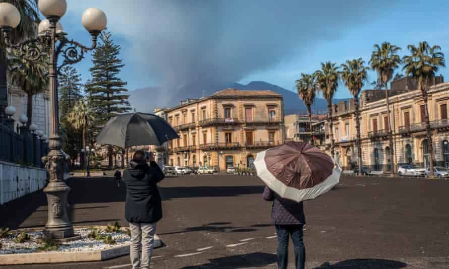 CItizen of Giarre cover their heads from volcanic ash from Mount Etna