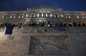 epa04807478 Demonstrators holds Greek and European flags as they protest on the parliament demanding that Greece remains in the Eurozone, outside the parliament in Athens, Greece, 18 June 2015.