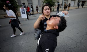 A protester pours water in the eyes of a friend affected by teargas during a protest in Raleigh, North Carolina.
