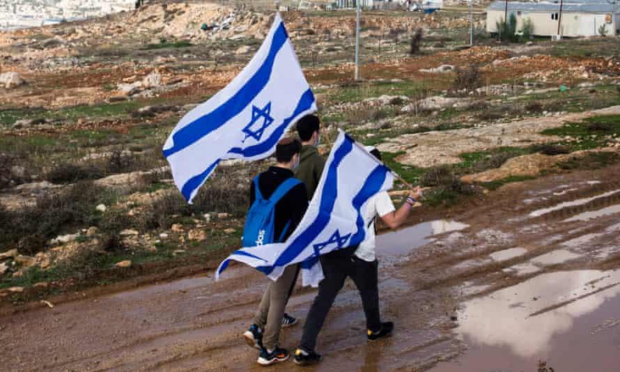 Israeli youths hold the Israeli flag as they are walking on Givat Hamatos on November 16, 2020 in Jerusalem, Israel.