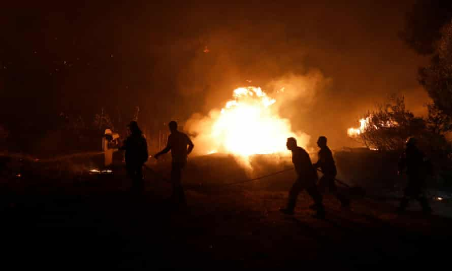 Firefighters try to extinguish a wildfire in the village of Rovies on Evia island as Greece fires continue to rage.