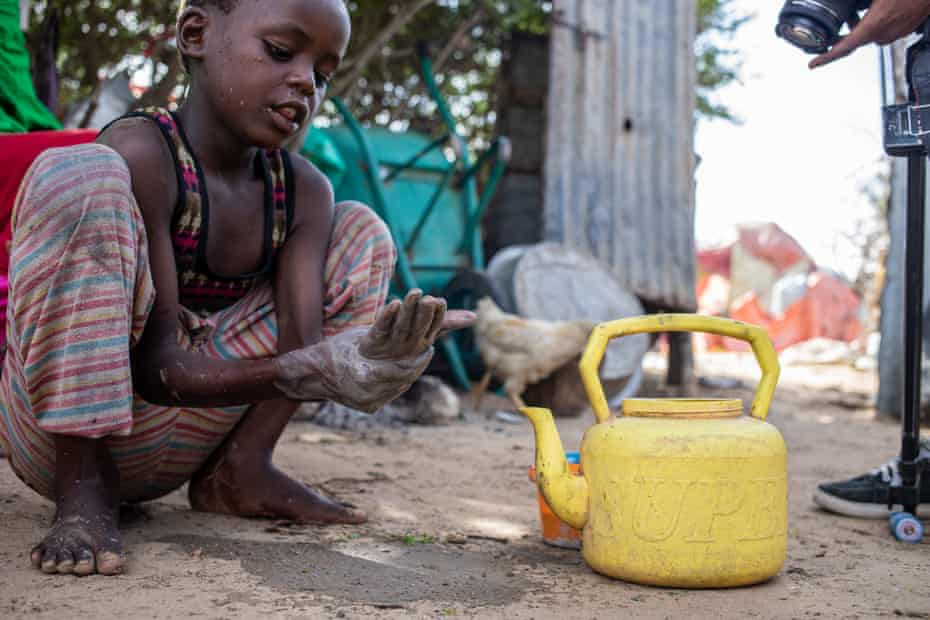 Ahmed Ali uses ash and soil to wash his hands outside his makeshift home at Xidig IDP camp in Mogadishu.