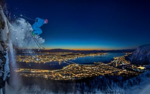 A skier descends a 10-metre high clifftop in Tromsø, Norway at night.