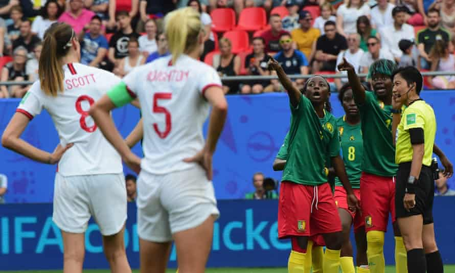 Cameroon's players protest referee Qin Liang's decision, urging her to go to VAR.