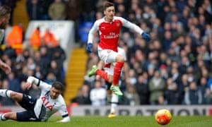 Mesut Özil skips past Kyle Walker.