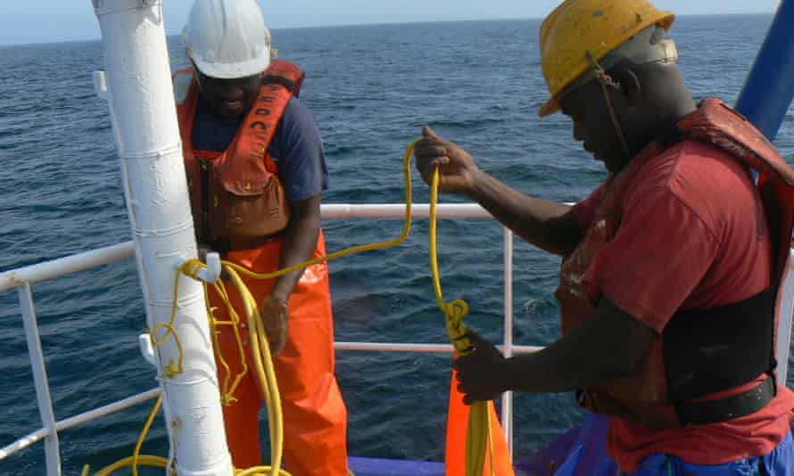 Crewmen attaching bird-scaring lines to an industrial trawler in Namibia.