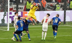 Gianluigi Donnarumma of Italy collects the ball ahead of Harry Maguire of England