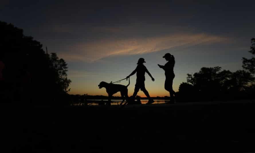 A couple walks their dog around Woodlawn Lake in San Antonio, Texas.