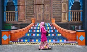 A woman walks past a mural in Kuala Lumpu, Malaysia.