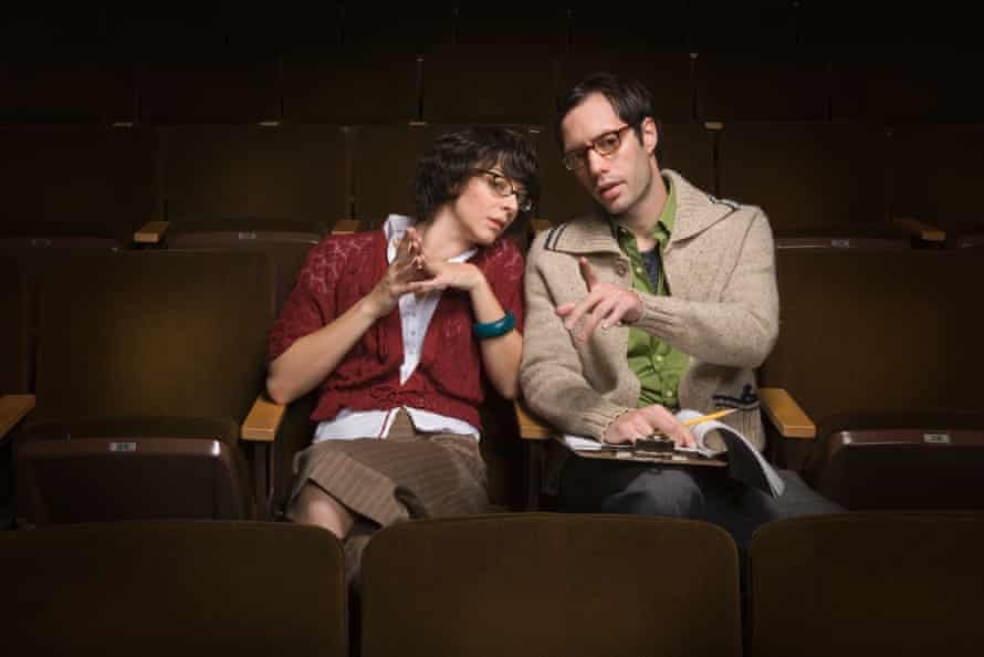 Man and woman talk in an empty theatre