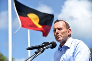Tony Abbott with Aboriginal flag behind him