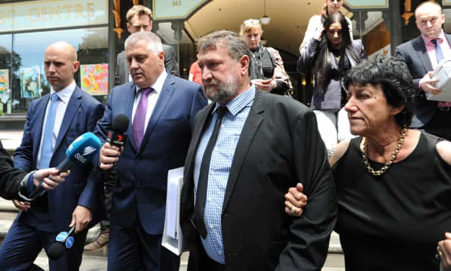 Greg (centre) and Virginia Hughes, the parents of cricketer Phillip Hughes, leave the Downing Centre Court in Sydney, Friday, 14 October.