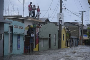 People look down on a flooded street from a roof in Santiago de los Caballeros, Dominican Republic