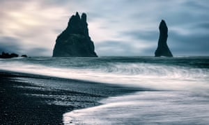 The beach near Vík in south Iceland with sea stacks in the distance.