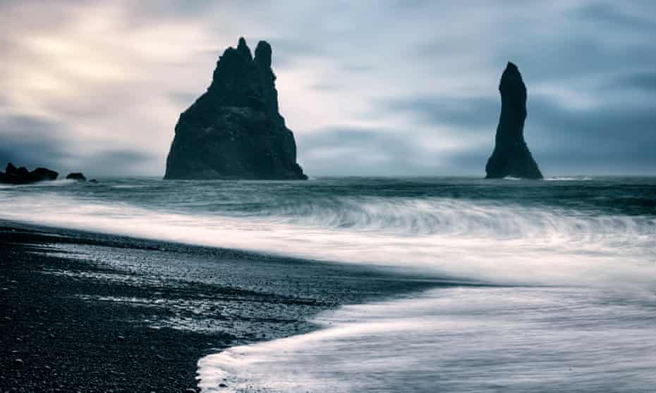 Vík's beach with black shingle and black rocks jutting out of the sea