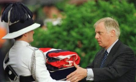 Chris Patten recebe uma bandeira britânica dobrada após sua queda no Palácio do Governo em Hong Kong, em junho de 1997.