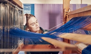 Hannah Robson seen across the blue threads of her loom