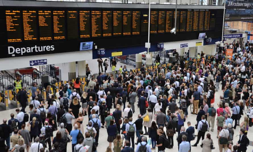 rail commuters look at the departures board at London Waterloo